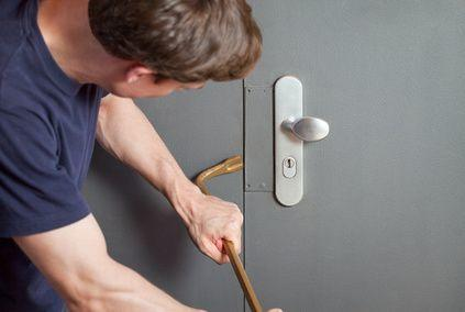 Brechstange an grauer Tür